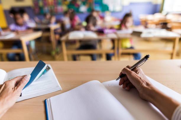 close up of unrecognizable teacher taking notes on a class. - professore di scuola superiore foto e immagini stock