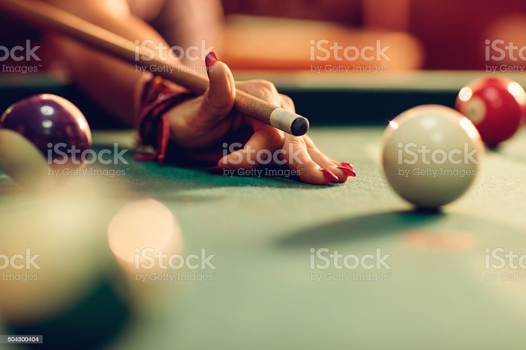 Close up of unrecognizable woman aiming at pool ball. stock photo