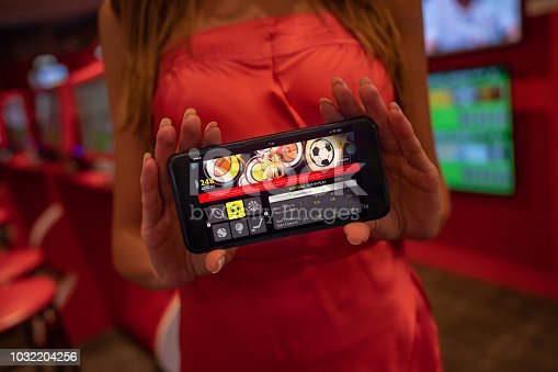 1032204252 istock photo Close up of unrecognizable woman holding a smartphone while showing a live sports betting application 1032204256