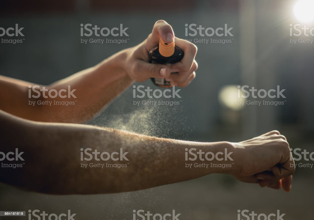 Close up of unrecognizable woman spraying moisturizer on her arm. royalty-free stock photo