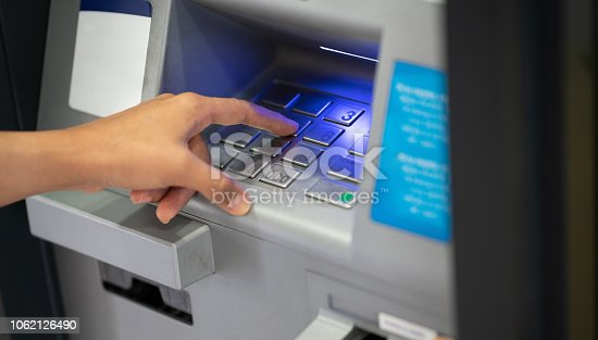 istock Close up of unrecognizable woman withdrawing cash from ATM putting PIN entry 1062126490
