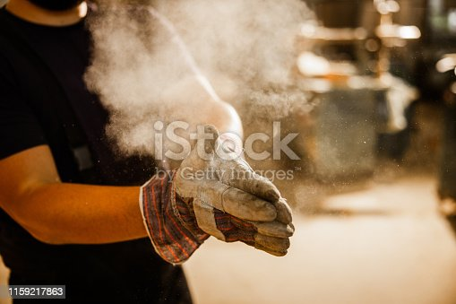 Close up of unrecognizable manual worker cleaning sawdust from his protective gloves in a workshop.