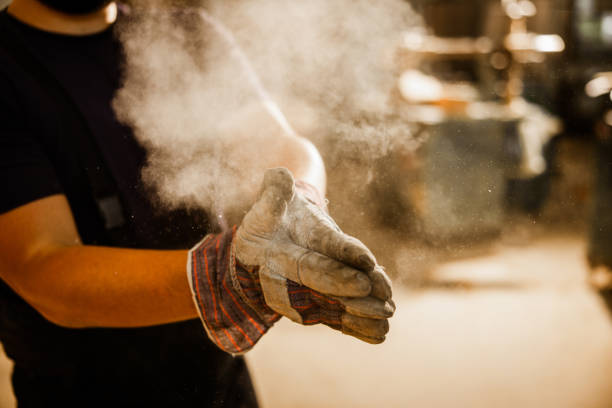 close up of unrecognizable worker cleaning dust from his gloves. - pył zdjęcia i obrazy z banku zdjęć