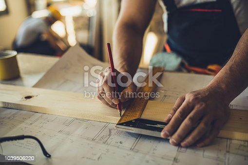 istock Close up of unrecognizable worker drawing on wood plank. 1039506220