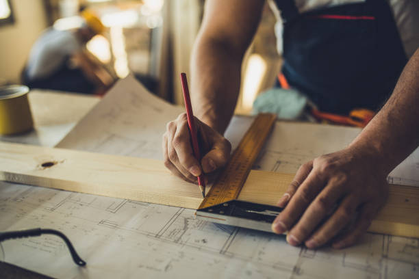 Close up of unrecognizable worker drawing on wood plank. Close up of unrecognizable carpenter making measurements and drawing on a plank. public housing stock pictures, royalty-free photos & images
