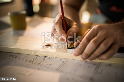 istock Close up of unrecognizable worker drawing on wood plank. 891274462