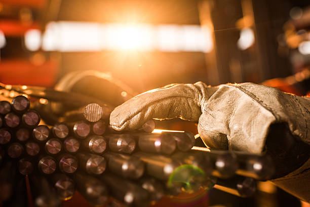 Close up of unrecognizable worker with stack of metal tubes. stock photo