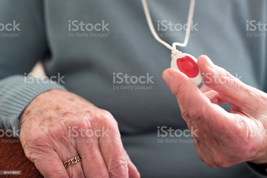 Close Up Of Unwell Senior Woman Holding Personal Alarm Button At Home stock photo