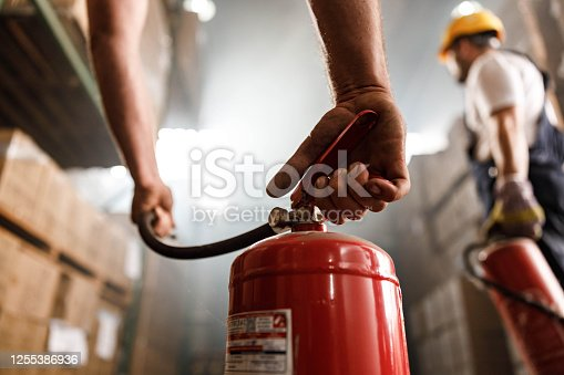 Close up of unrecognizable worker using fire extinguisher in a storage room.