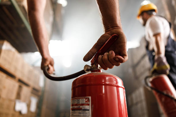 Close up of using fire extinguisher in a warehouse. stock photo