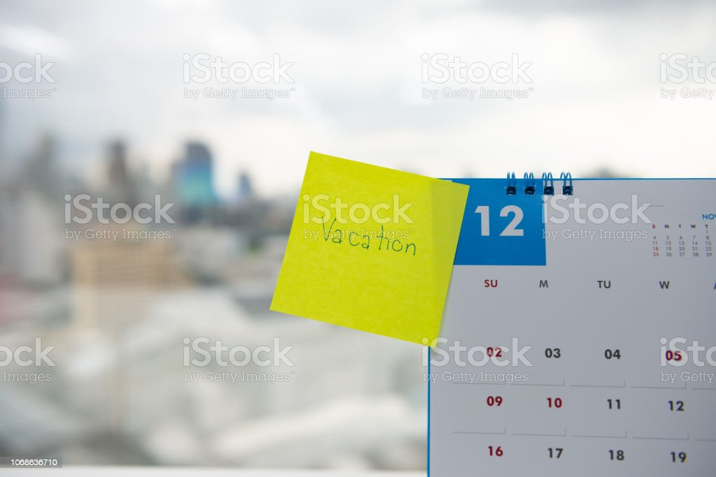 Close up of vacation on paper note stick on the calendar of December for year end holidays concept stock photo