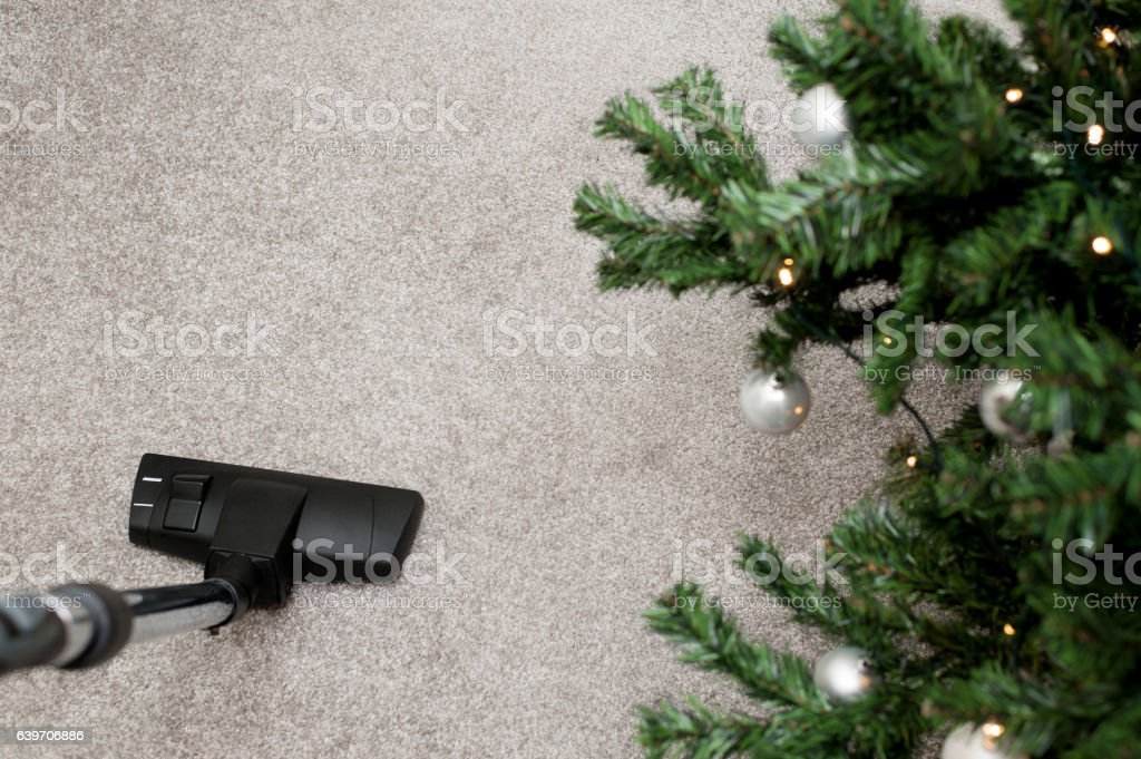 Close up of vacuum cleaner nozzle cleaning carpet at home stock photo