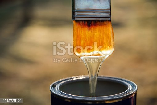 istock Close up of varnish dripping of paint brush. Brush with lacquer over can, nobody 1215725121