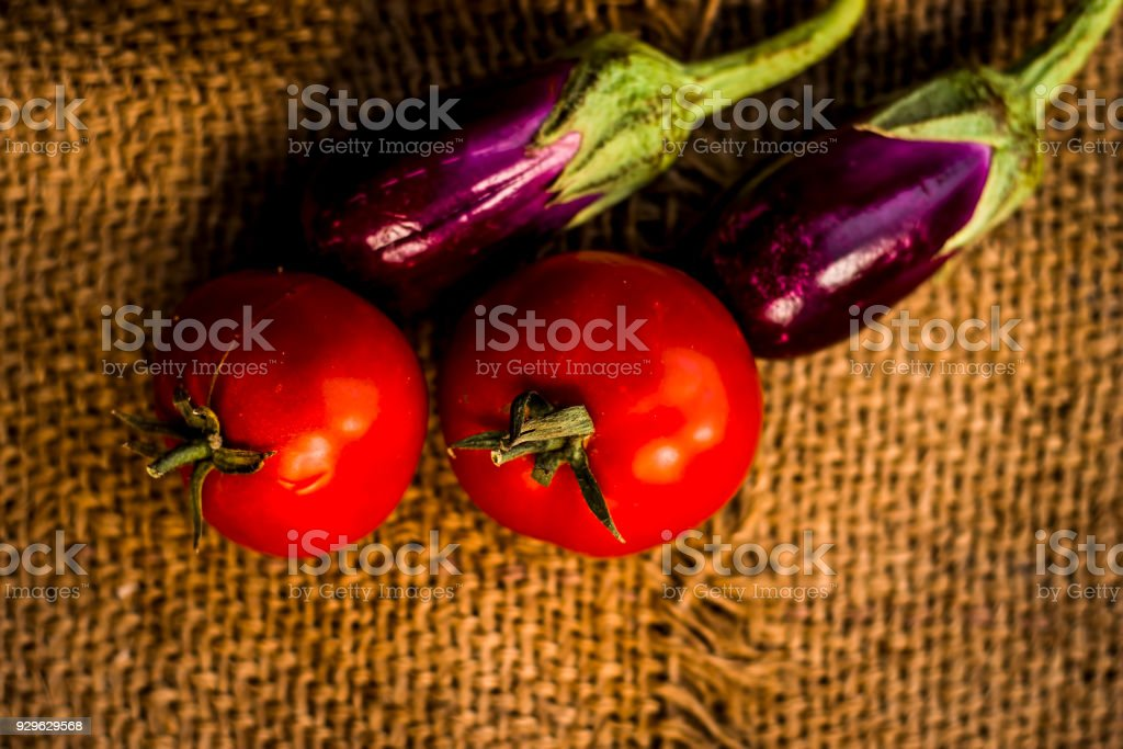 Close up of vegetables for a spicy Indian lunch i.e Egg plant,Solanum melongena & Tomato,Solanum lycopersicum on a gunny background. stock photo