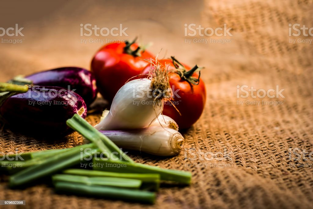 Close up of vegetables for a spicy Indian lunch i.e. Egg plant,Solanum melongena,Tomato,Solanum lycopersicum and spring onions,Allium fistulosum on a gunny background. stock photo