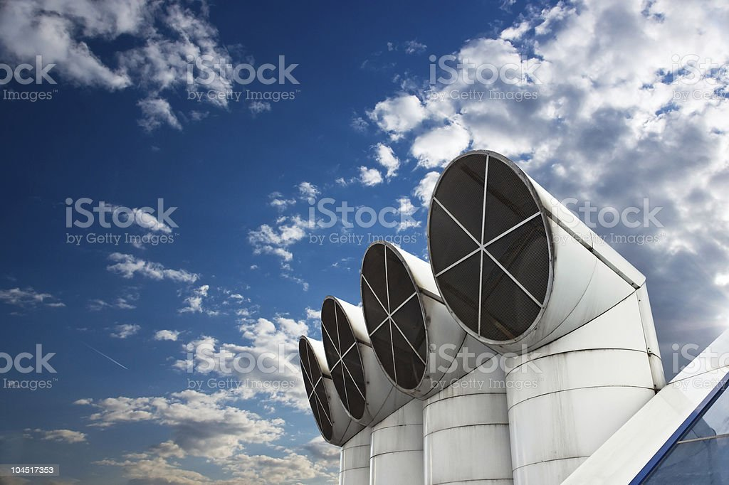 Close up of ventilation outlet pipes against blue cloudy sky royalty-free stock photo