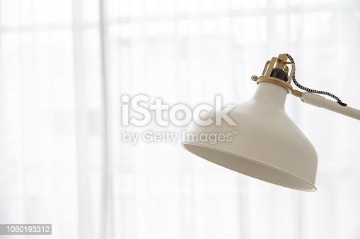 istock close up of vintage cream adjustable desk lamp on white light curtain background. 1050193312