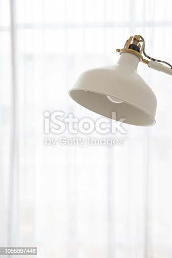 istock close up of vintage cream adjustable desk lamp on white light curtain background. 1055597448