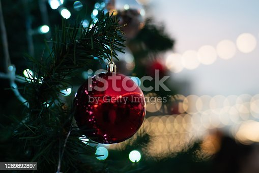 Close up of vintage toned red balls on christmas tree bokeh garlands in the background. New Year concept.