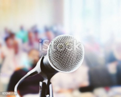 istock Close up of  vocal mic in front of defocussed audience 520981130