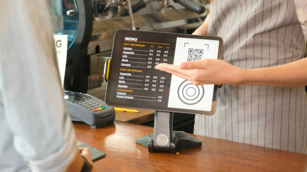 Close up of waitress hand showing coffee menu on digital tablet  to customer for ordering at counter coffee shop, small business food and drink concept stock photo