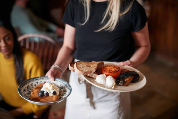 close up of waitress working in traditional english pub serviert frühstück für gäste - liebeskummer englisch stock-fotos und bilder