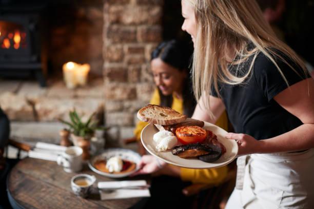 El primer plano de la camarera que trabaja en el pub inglés tradicional que sirve el desayuno a los huéspedes - foto de stock