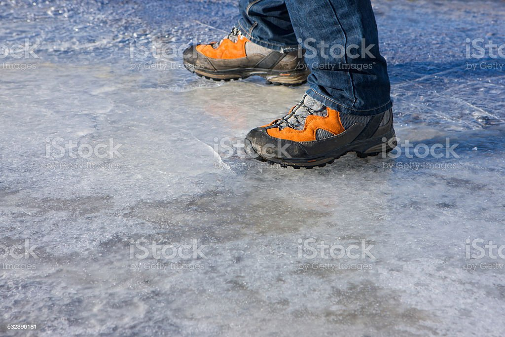 Close up of walking boots standing on cracking thin ice stock photo