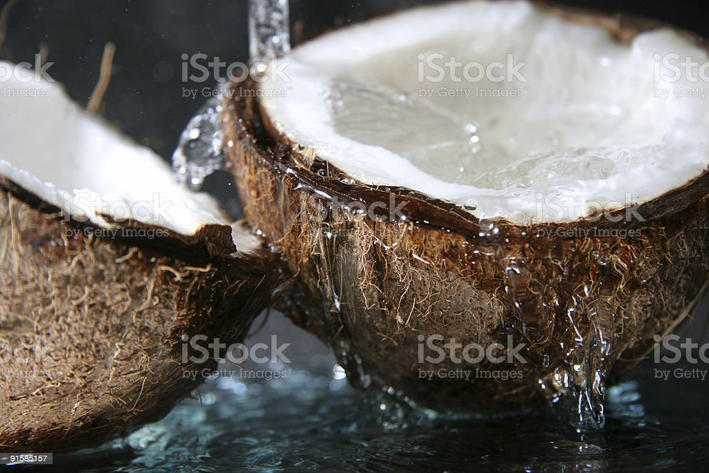 Close up of water dripping on split coconut stock photo