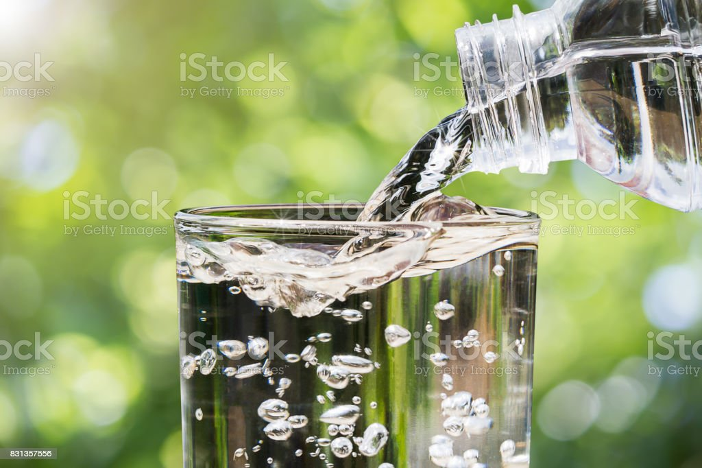 Close up of water flowing from drinking water bottle into glass on blurred green nature bokeh background, healthy drinking clean water concept - foto stock