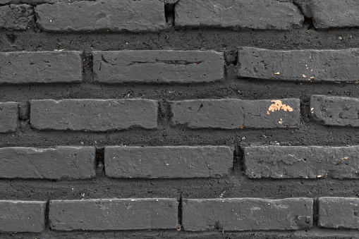905087856 istock photo close up of weathered black brick wall texture background. 1049679592
