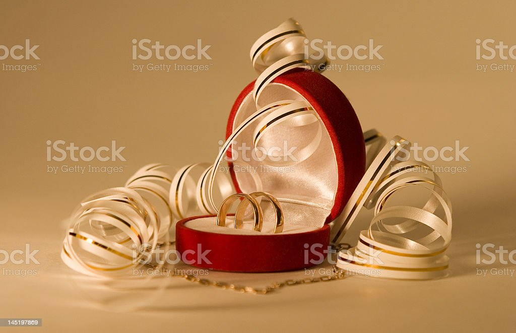 Close up of wedding bands over gold background royalty-free stock photo