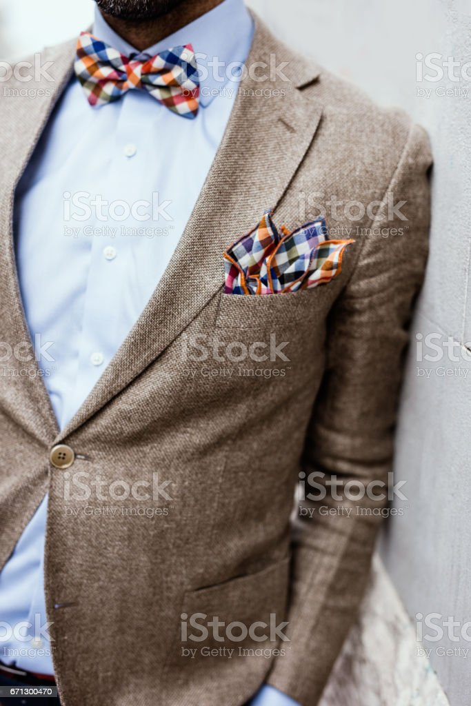 Close up of well dressed man leaned on the wall. Colorful bow tie and handkerchief, blue shirt and fancy jacket stock photo