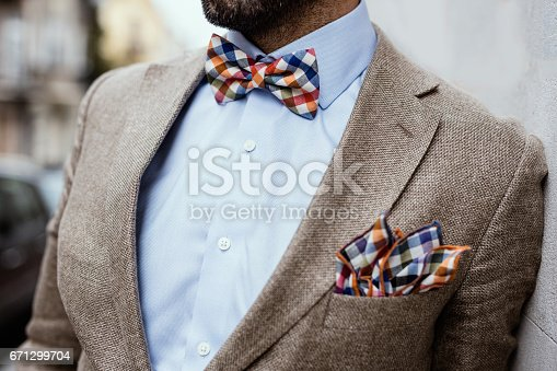 istock Close up of well dressed man's torso. Guy wearing jacket, shirt and colorful handkerchief and bow tie 671299704