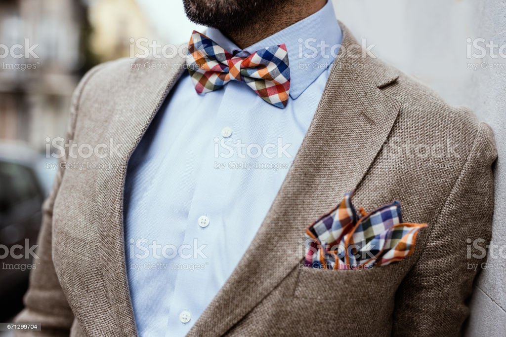 Close up of well dressed man's torso. Guy wearing jacket, shirt and colorful handkerchief and bow tie stock photo