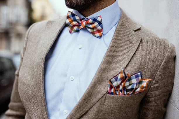 Close up of well dressed man's torso. Guy wearing jacket, shirt and colorful handkerchief and bow tie Close up of well dressed man's torso. Guy wearing jacket, shirt and colorful handkerchief and bow tie bow tie stock pictures, royalty-free photos & images