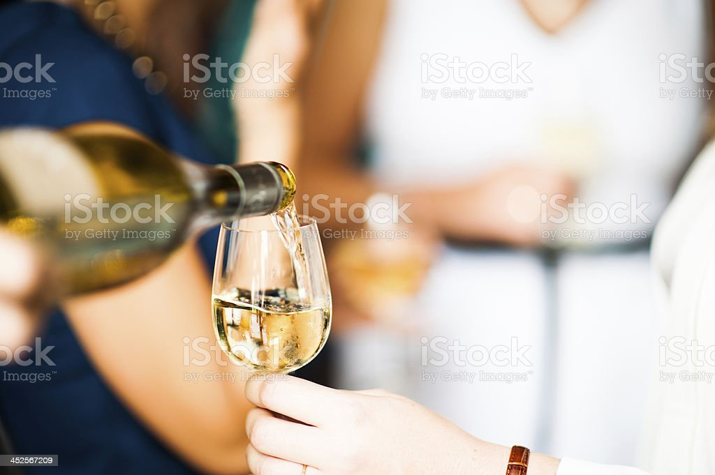 Close up of white wine being poured into glass stock photo