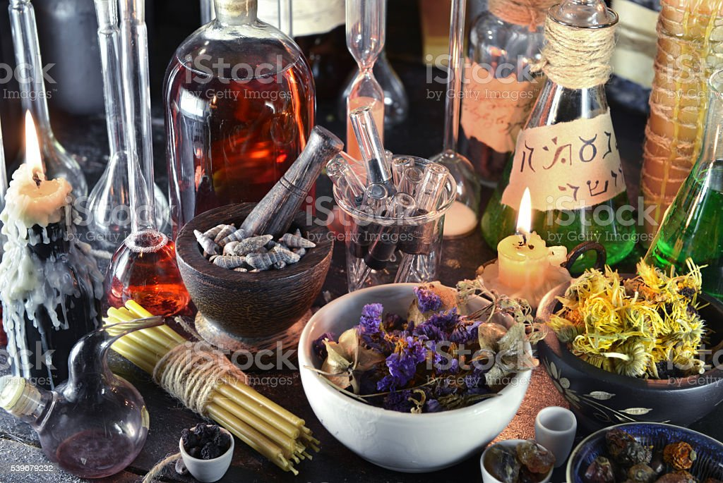 Close up of witch laboratory with candles and alchemy glassware stock photo