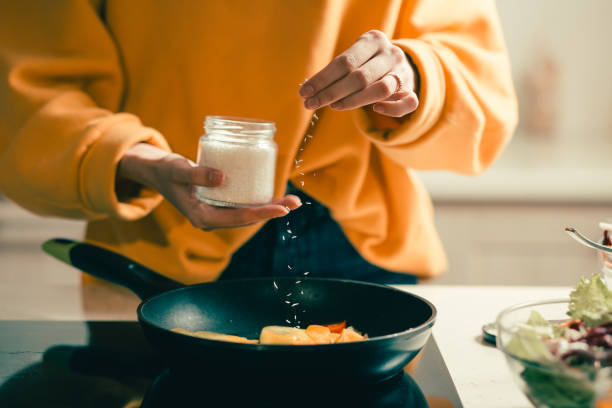Close up of woman adding coconut flakes to the meal stock photo