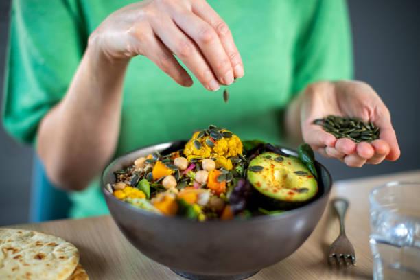 Nahaufnahme der Frau Hinzufügen von Kürbiskernen zu gesunden veganen Mahlzeit in Schüssel – Foto