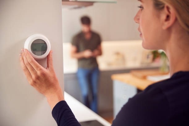 Close Up Of Woman Adjusting Wall Mounted Digital Central Heating Thermostat Control At Home stock photo