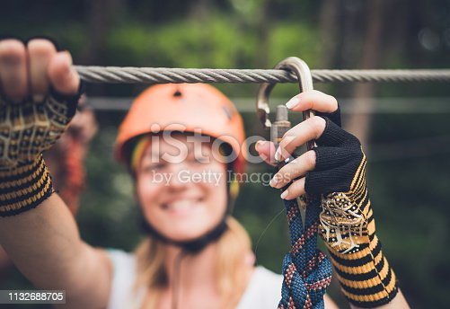 Close up of a woman adjusting her zip line while being on canopy tour in nature.