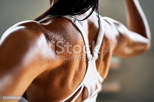 istock Close up of woman back with flexing her muscles 1210253197
