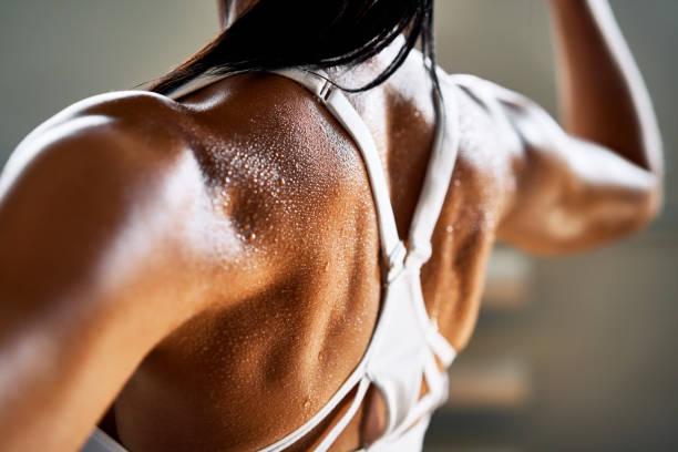 Primer plano de la mujer hacia atrás con flexionar sus músculos - foto de stock