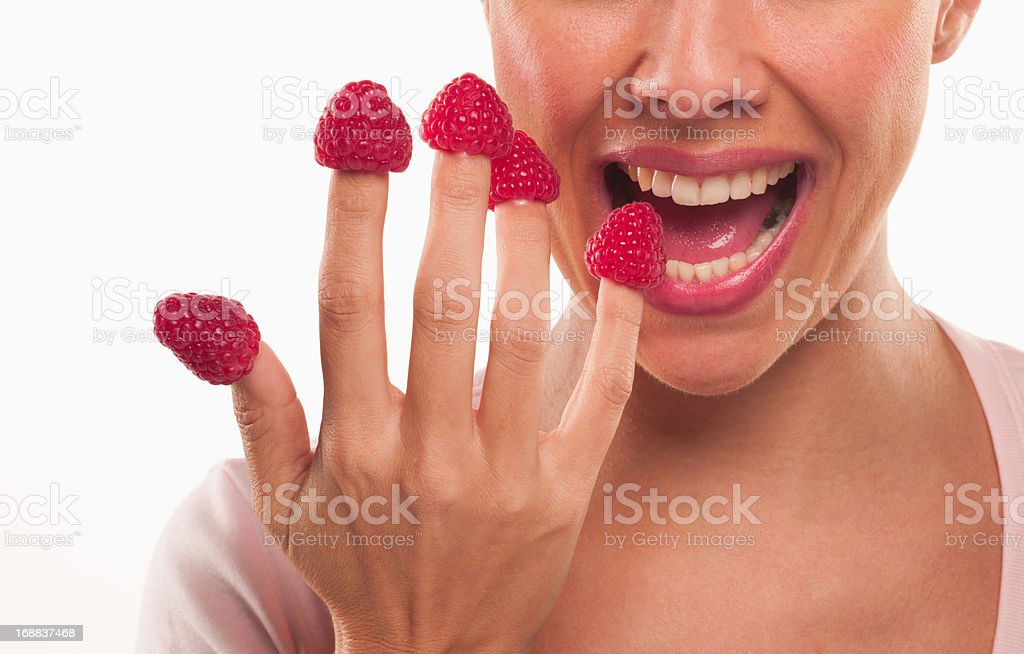 Close up of woman biting raspberries on fingertips stock photo