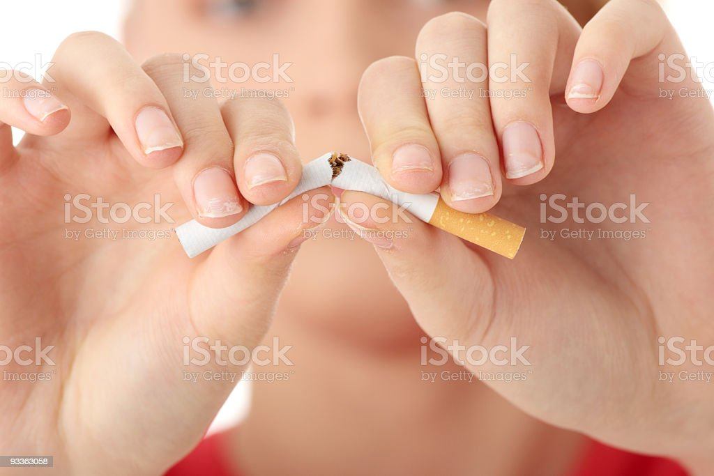 Close up of woman braking a cigarette in half stock photo