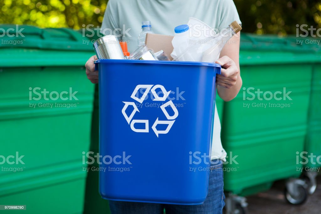 Close Up Of Woman Carrying Recycling Bin stock photo