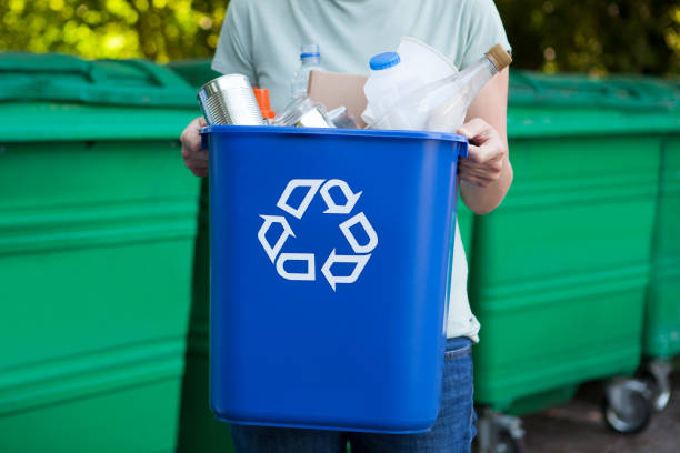 close up of woman carrying recycling bin - recycling bin stock photos and pictures
