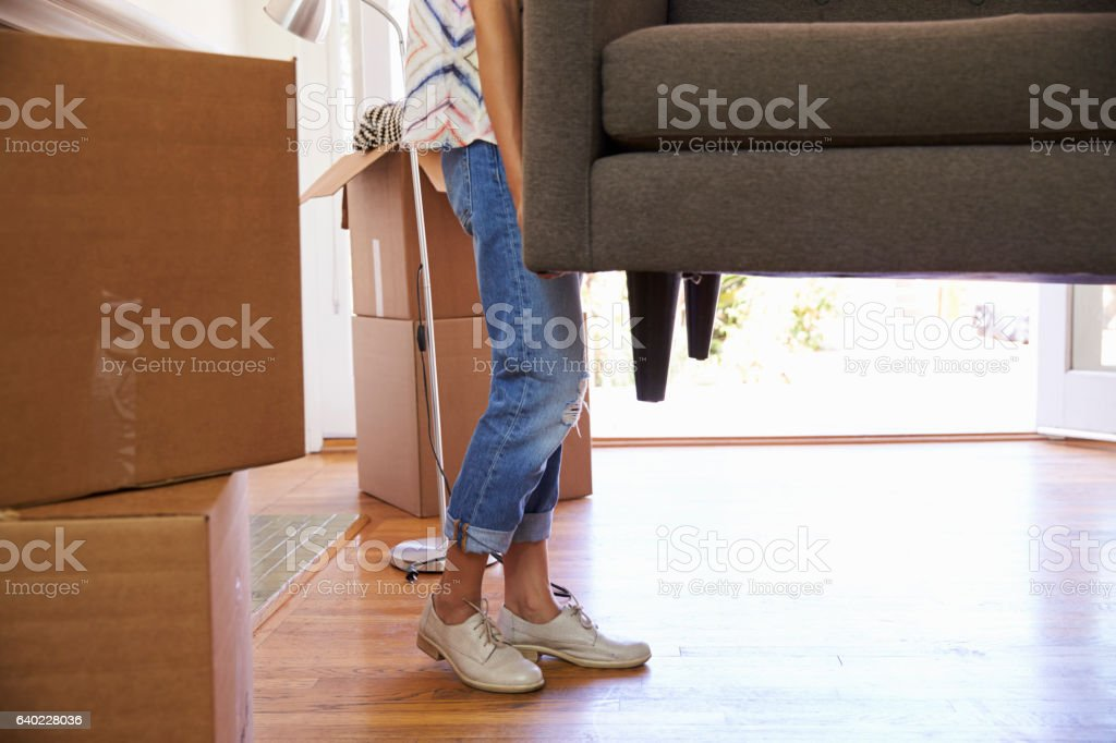 Close Up Of Woman Carrying Sofa Into New Home On Moving stock photo