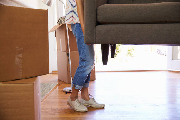 close up of woman carrying sofa into new home on moving - relocation stock photos and pictures
